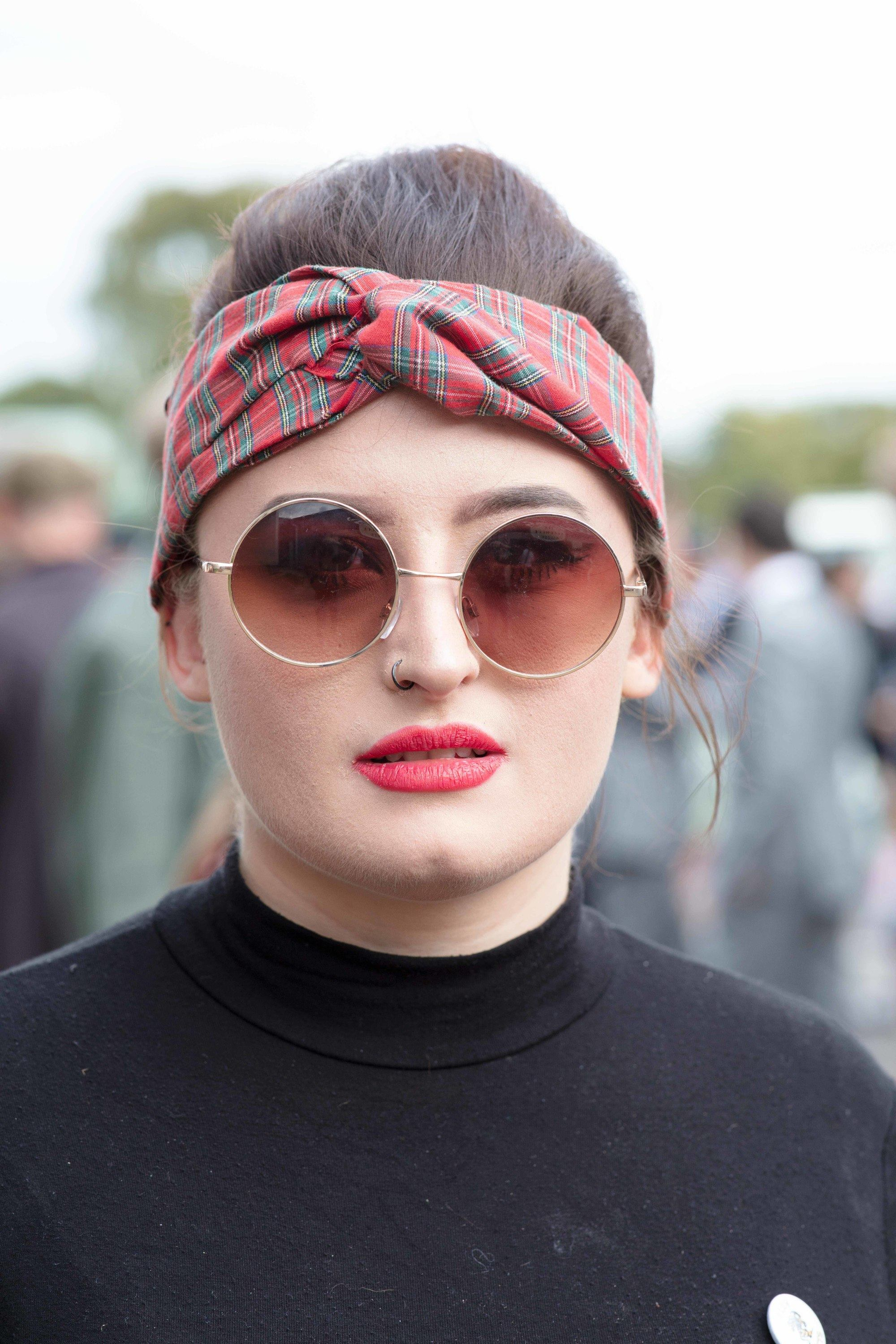 Retro hairstyles: Close up shot of a woman with dark brown hair styled into a beehive updo with a headwrap, wearing black and John Lennon style glasses at Goodwood festival