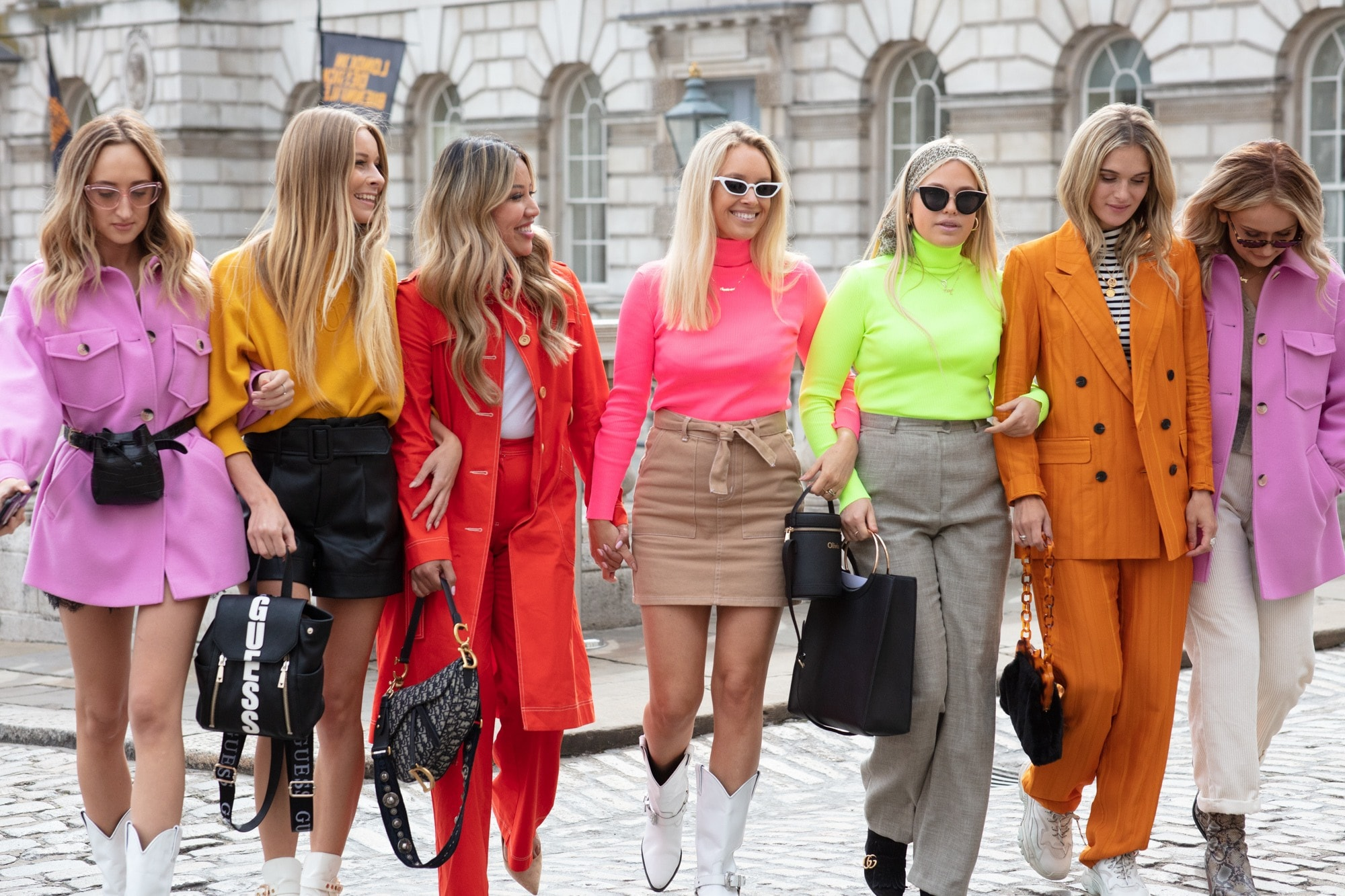 London Fashion Week street style hair: Close up shot of a group of street style women with various shades of blonde hair, wearing bright orange and pink clothing while posing together