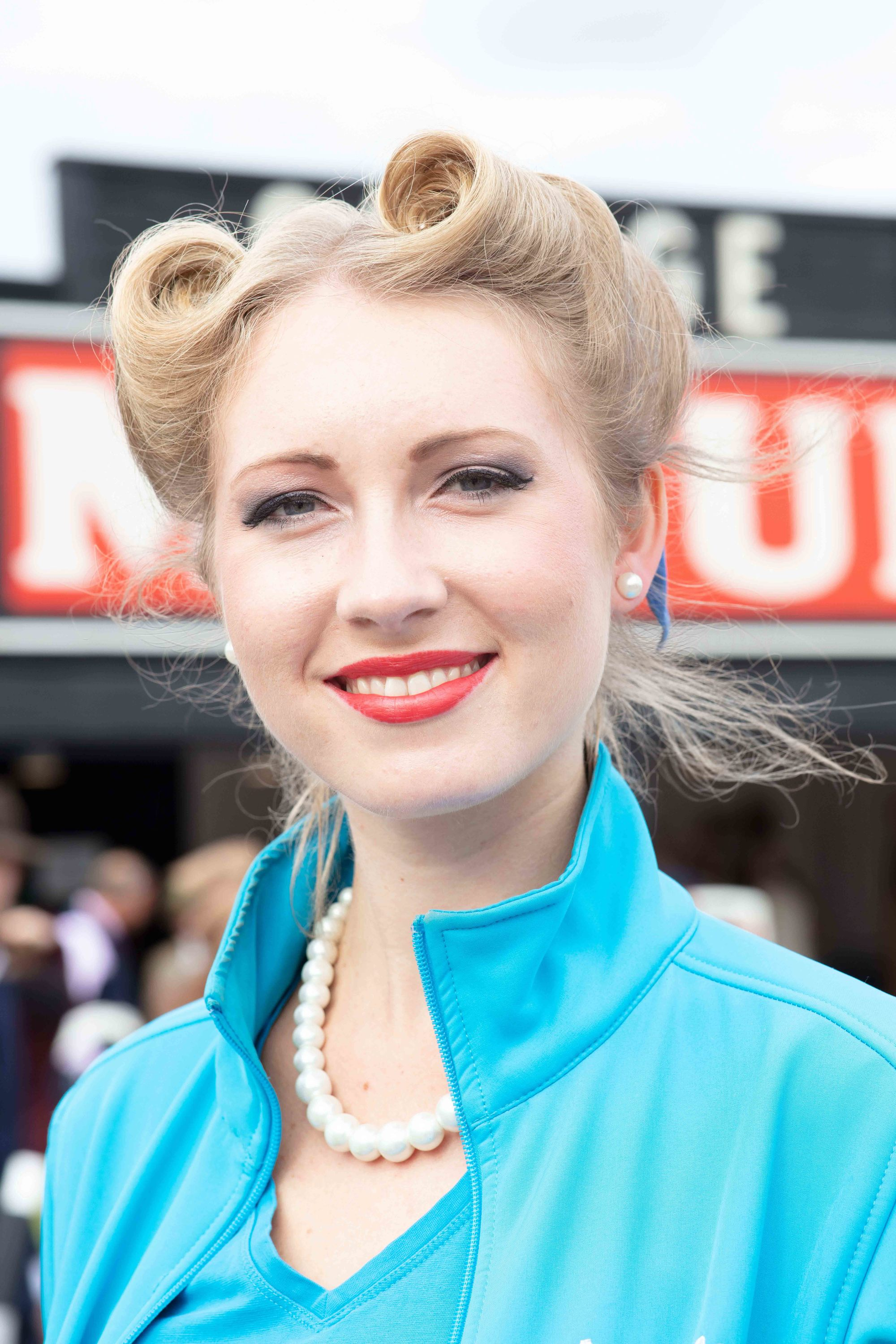 Pin up hairstyles: Blonde at Goodwood Revival with her hair in a victory rolls updo