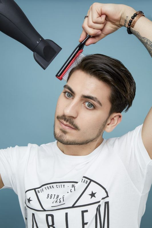 How to blow dry men's hair: Brown haired man with hair swept to one side using a plastic brush to dry his hair