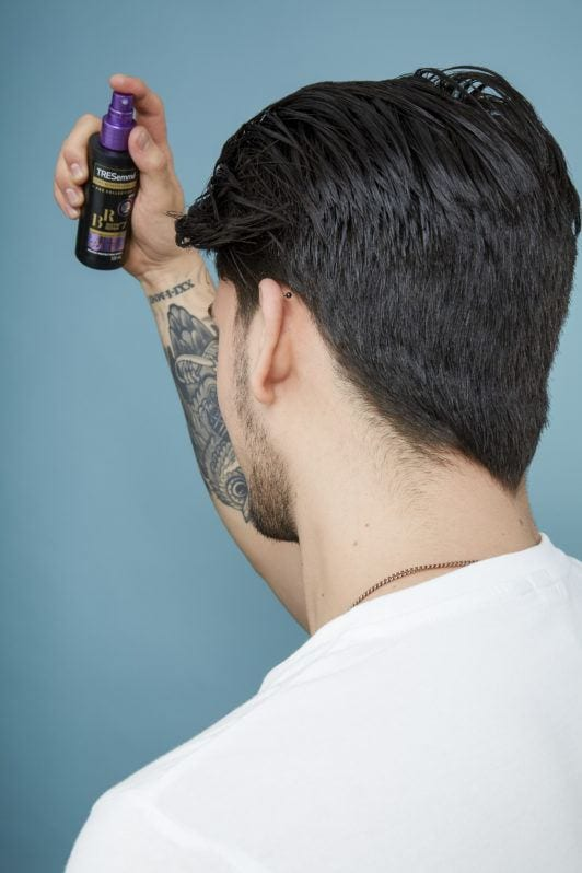 How to blow dry men's hair: Back view of a brown haired man with wet hair spraying Tresemme primer on his hair, wearing a white t-shirt