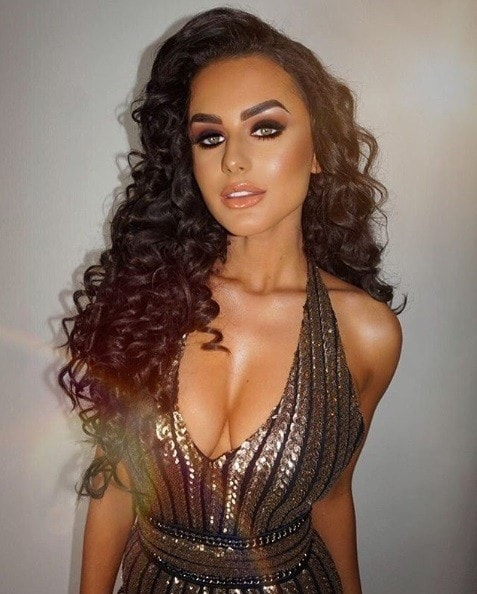 Club hairstyles: Amber Davies from Love Island with long brunette hair styled in corkscrew curls, wearing a plunging sequin dress