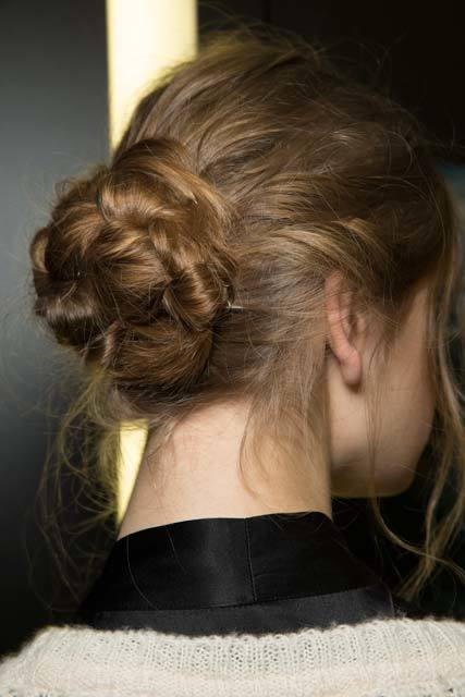 Knot bun hairstyle: Close-up shot from behind of a brunette model with a messy braided bun with wispy strands