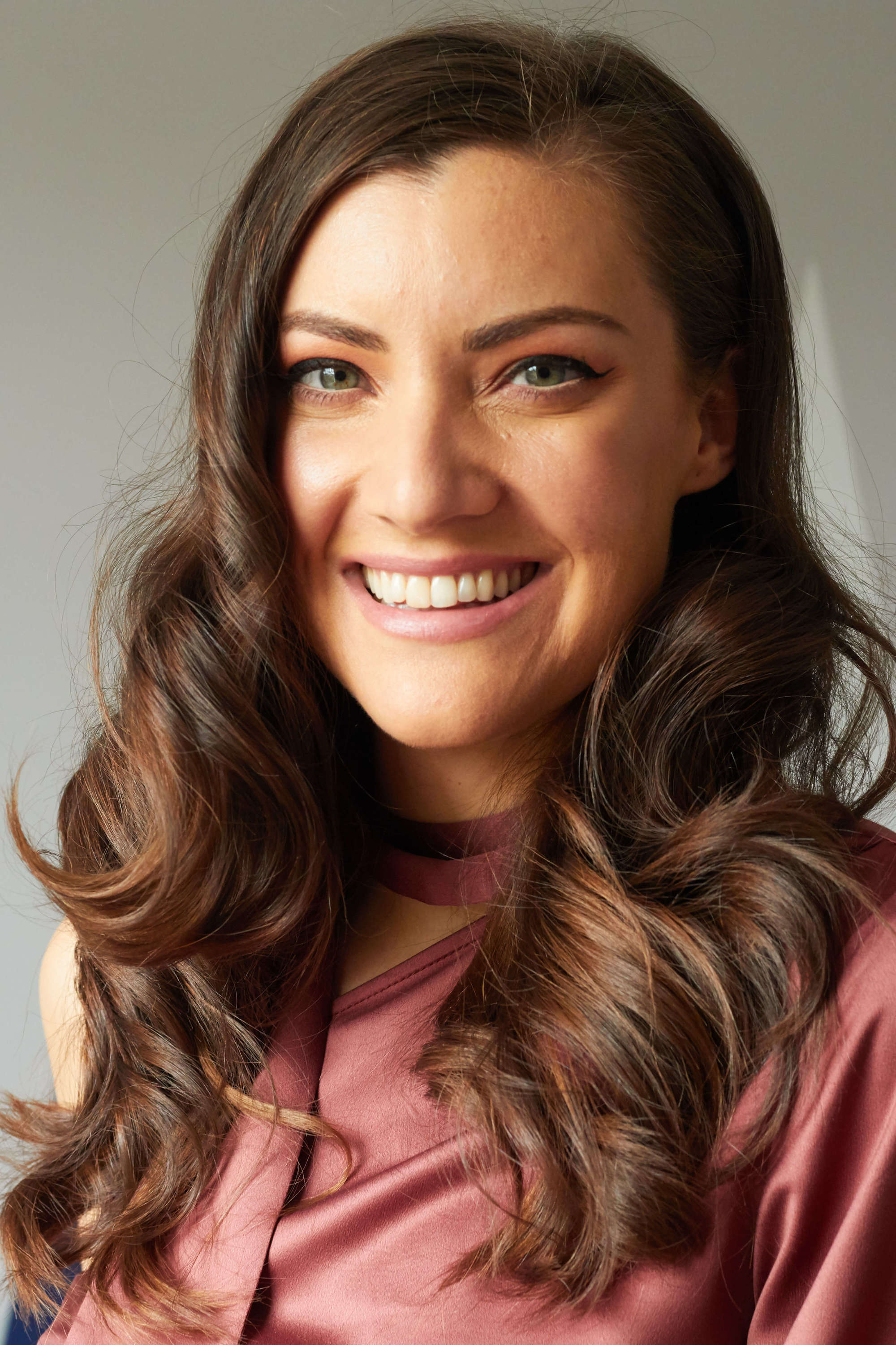 Woman with dark long hair styled into Hollywood Waves