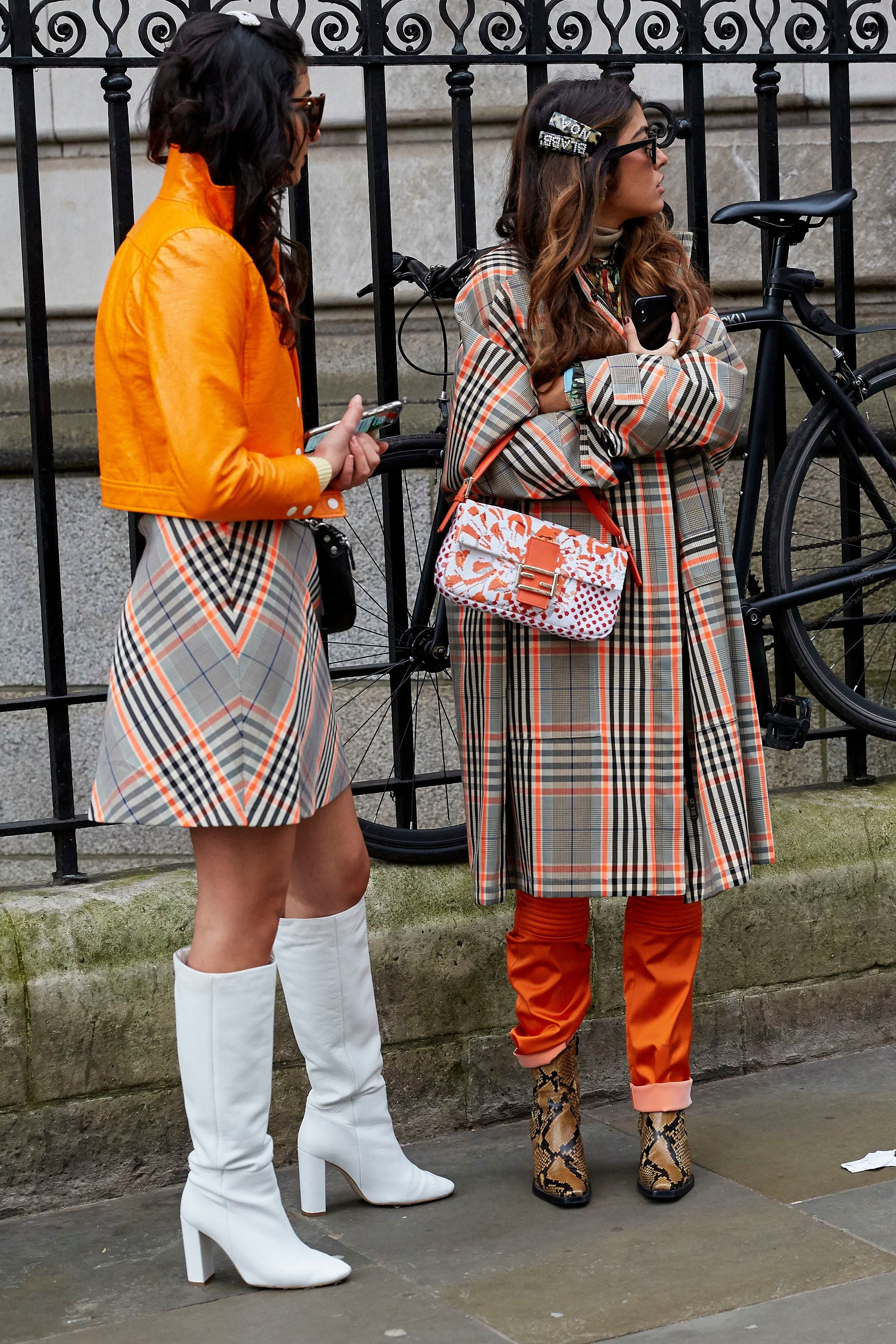 LFW hair street style: Two women with long brown hair with bold hair clips wearing checked outfits.