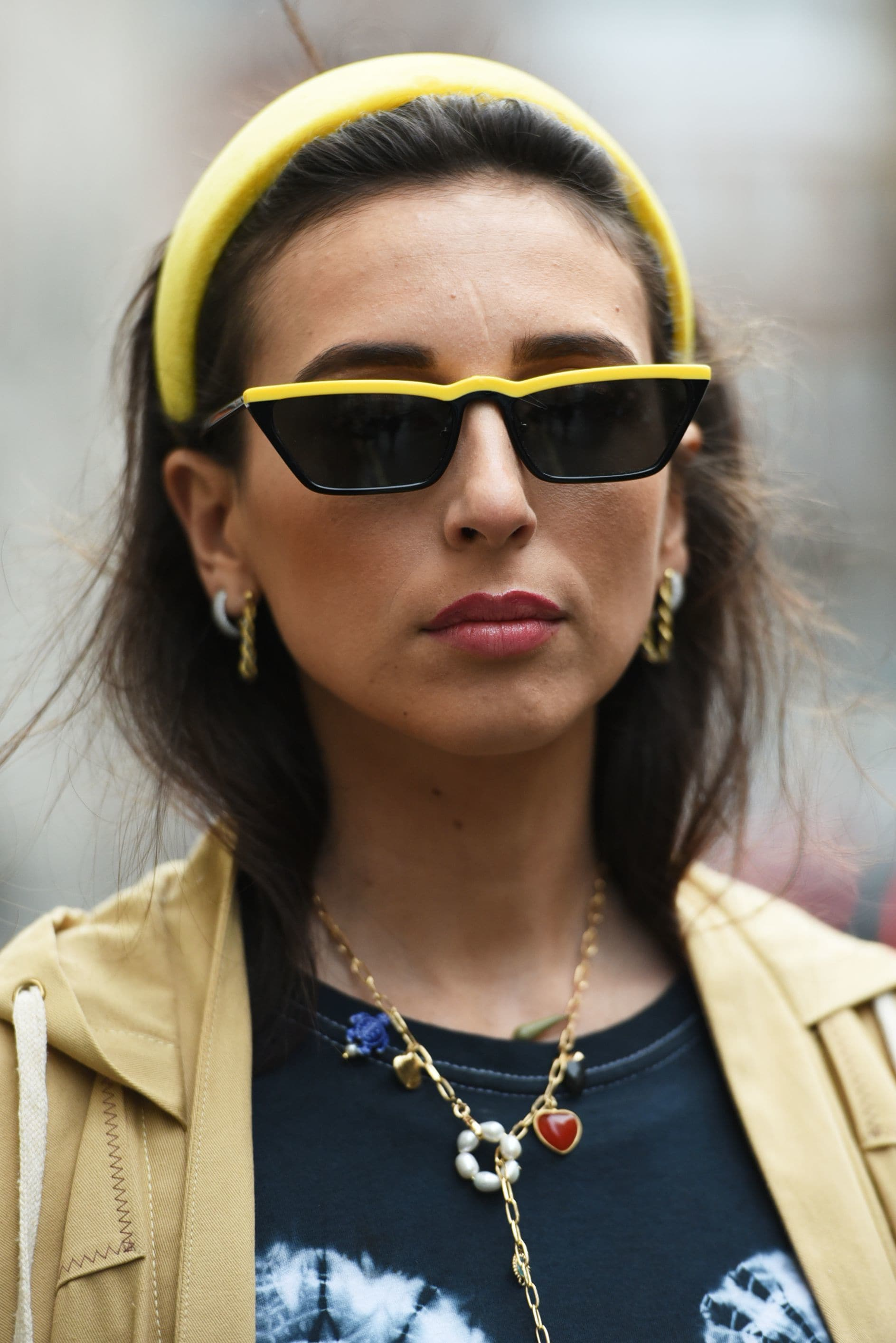 LFW hair street style: Woman with brown hair tucked into a beige jacket wearing a yellow headband and black and yellow sunglasses.