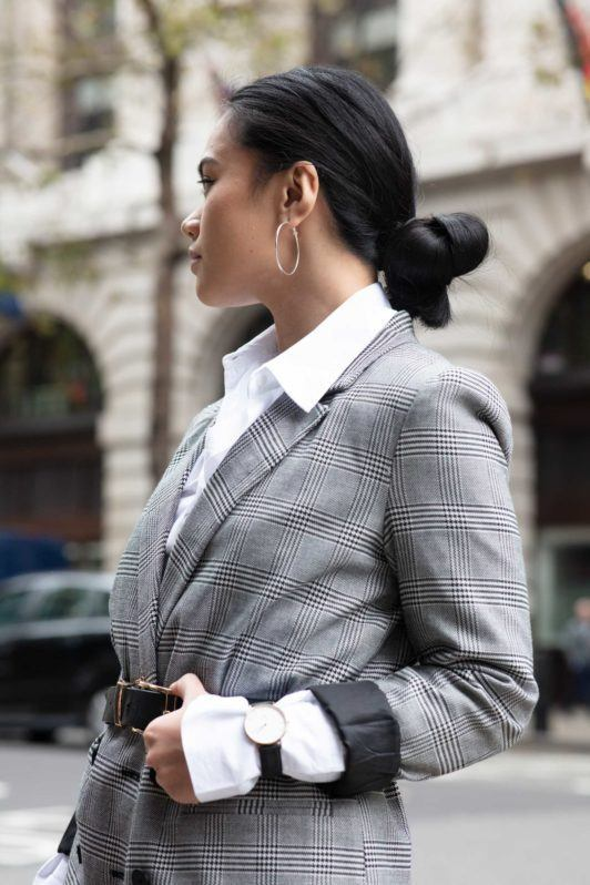 Knot bun hairstyle: Close up shot of a woman with a dark low knot bun wearing checked jacket with white top, wearing belt bag and posing on the street