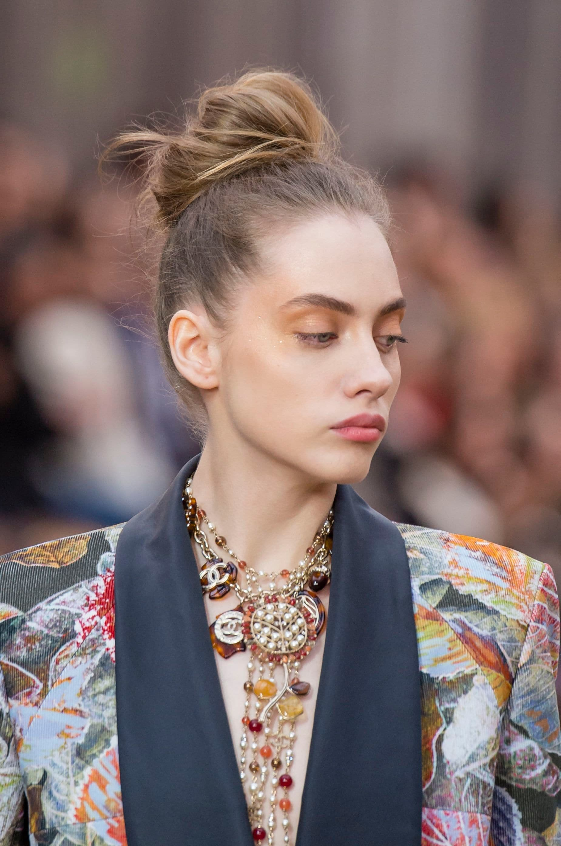 Knot bun hairstyle: Runway picture of a woman with light brunette hair in a loose messy top knot