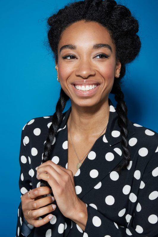 Blow out natural hair: Smiling natural haired woman with half of her hair up and the bottom layers twisted into two rope braids.