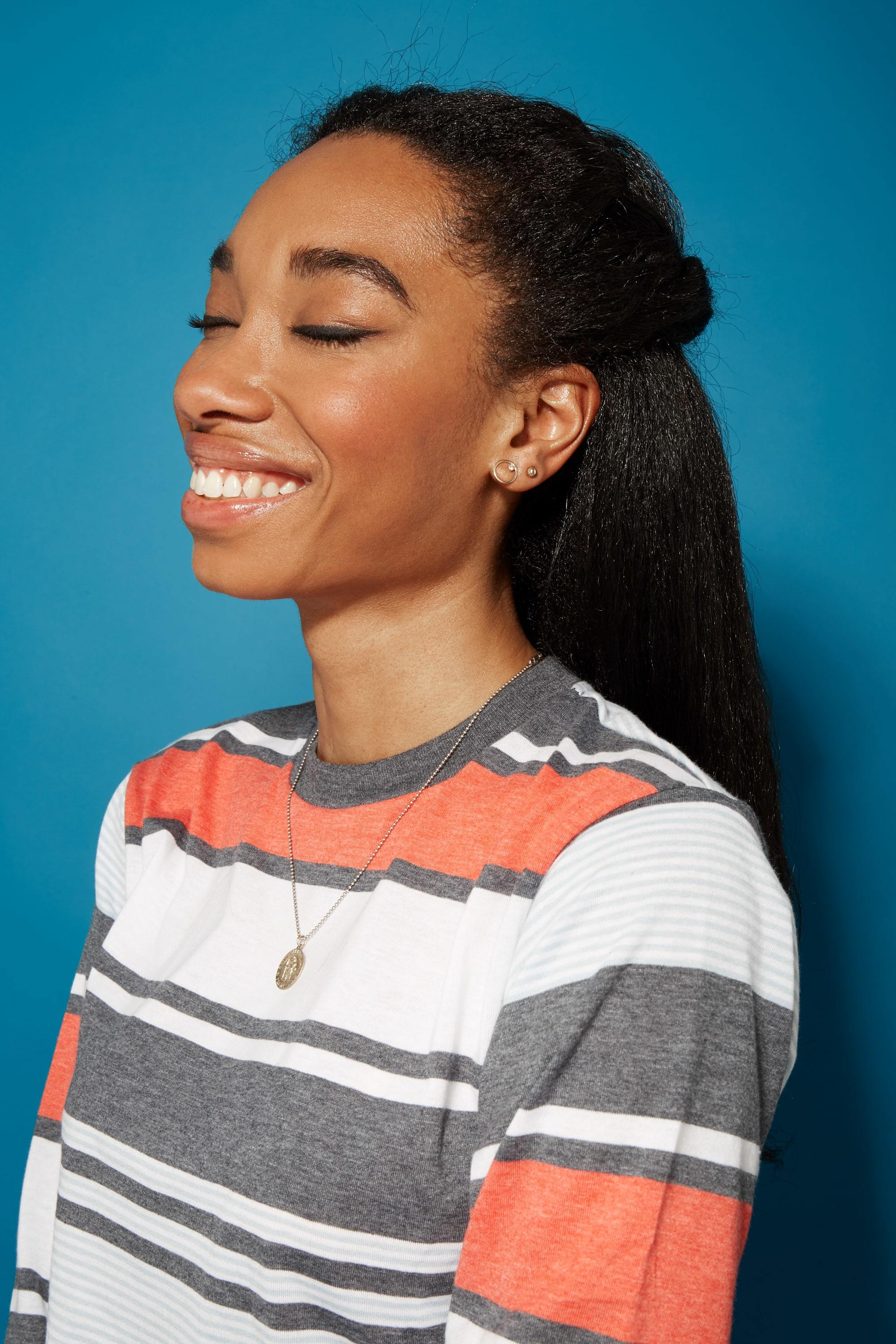 Blow out natural hair: Smiling woman with straightened natural hair in a half-up half-down hairstyle