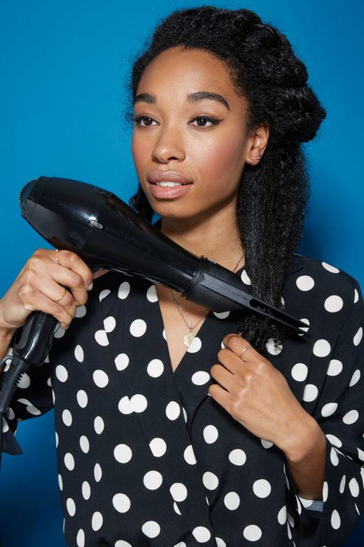 Blow out natural hair: Woman with dark brown natural hair using a hairdryer and pik attachment to blow dry her hair straight