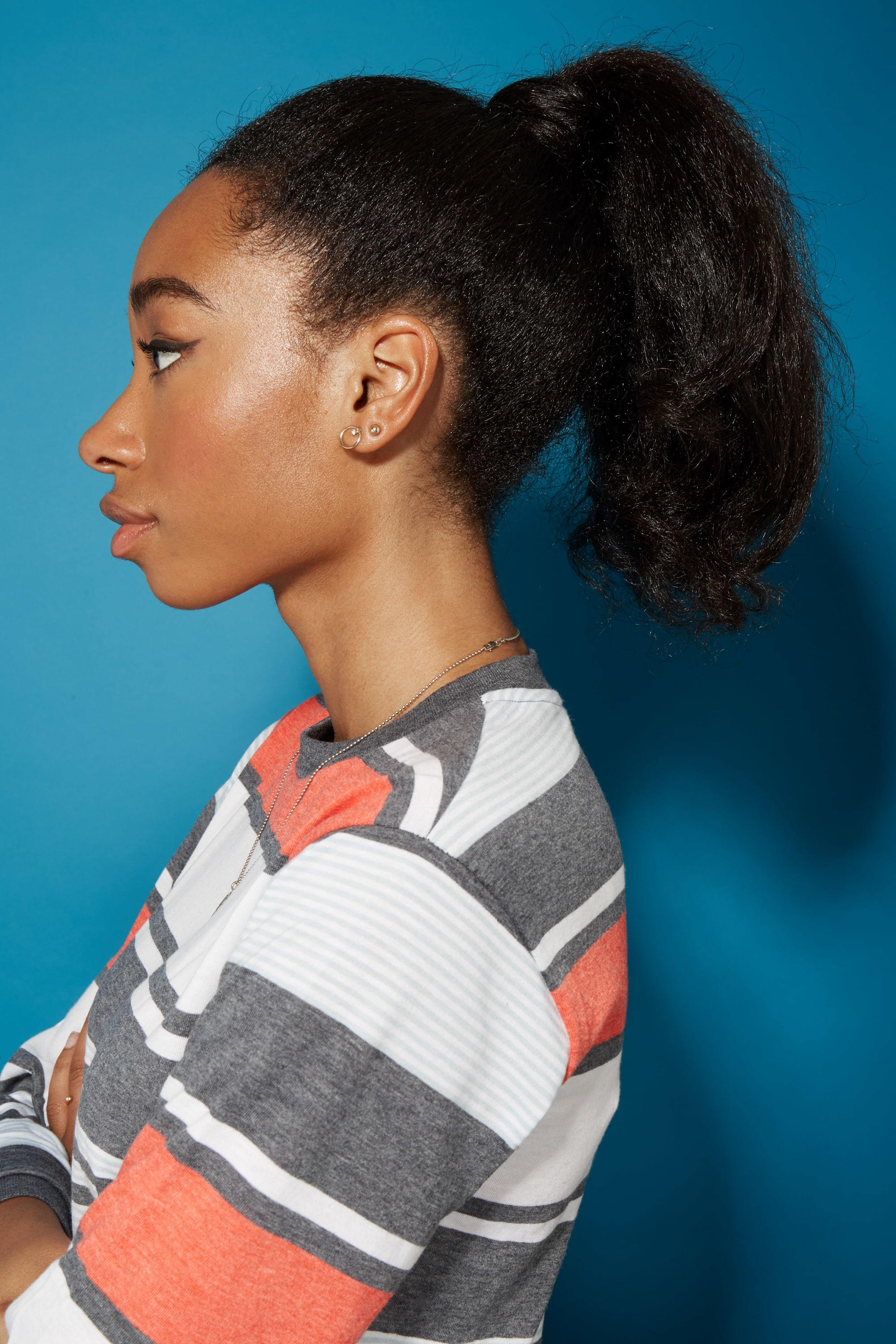Blow out natural hair: Side profile of a woman with straightened natural hair in a high wrapped ponytail wearing a striped top.