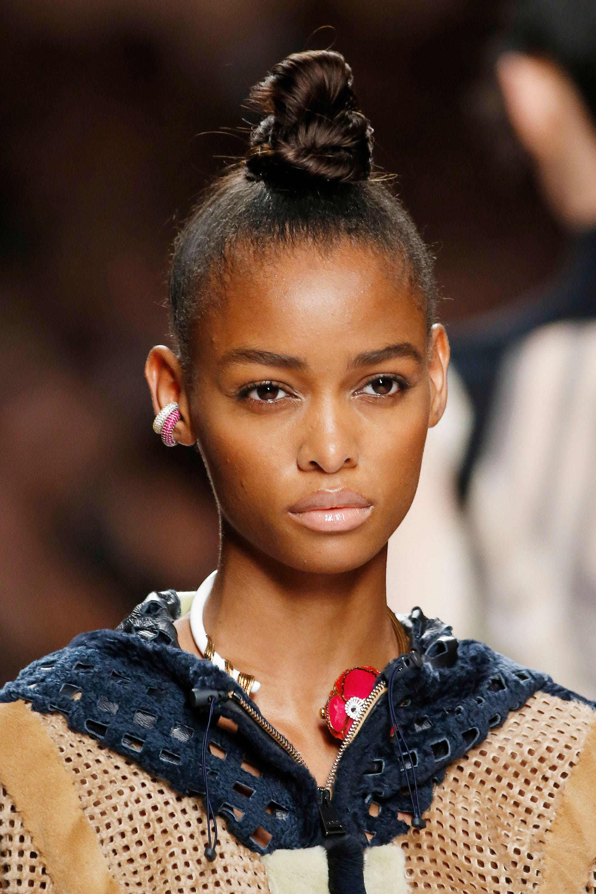 Knot bun hairstyle: Runway picture of a woman with a tight slicked back ninja bun top knot hairstyle