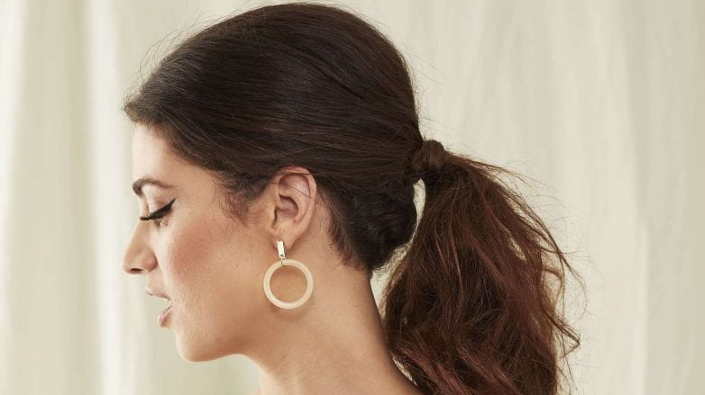 Woman with her dark long her styled into Bardot ponytail