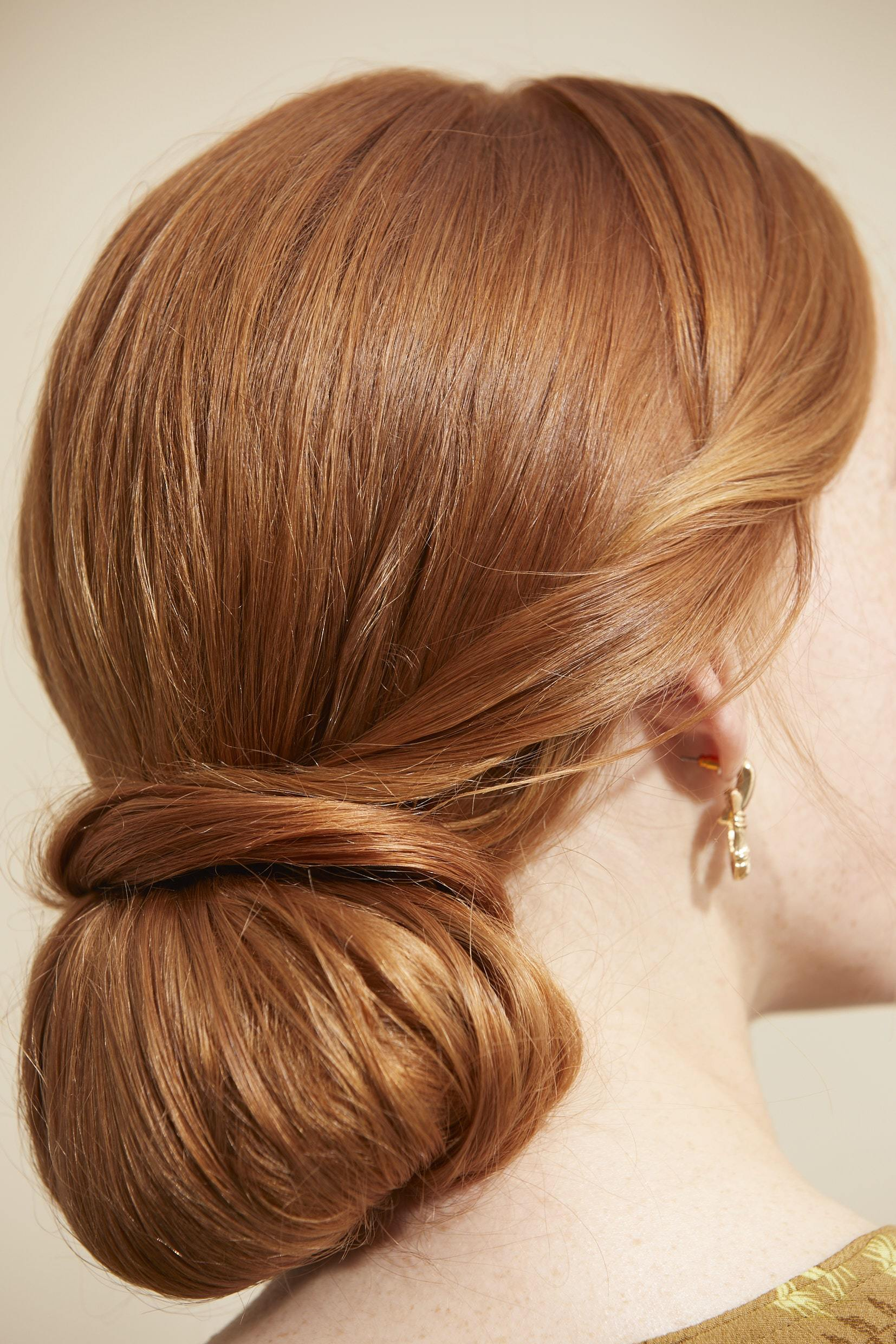 Woman with red hair styled into a retro twisted low bun