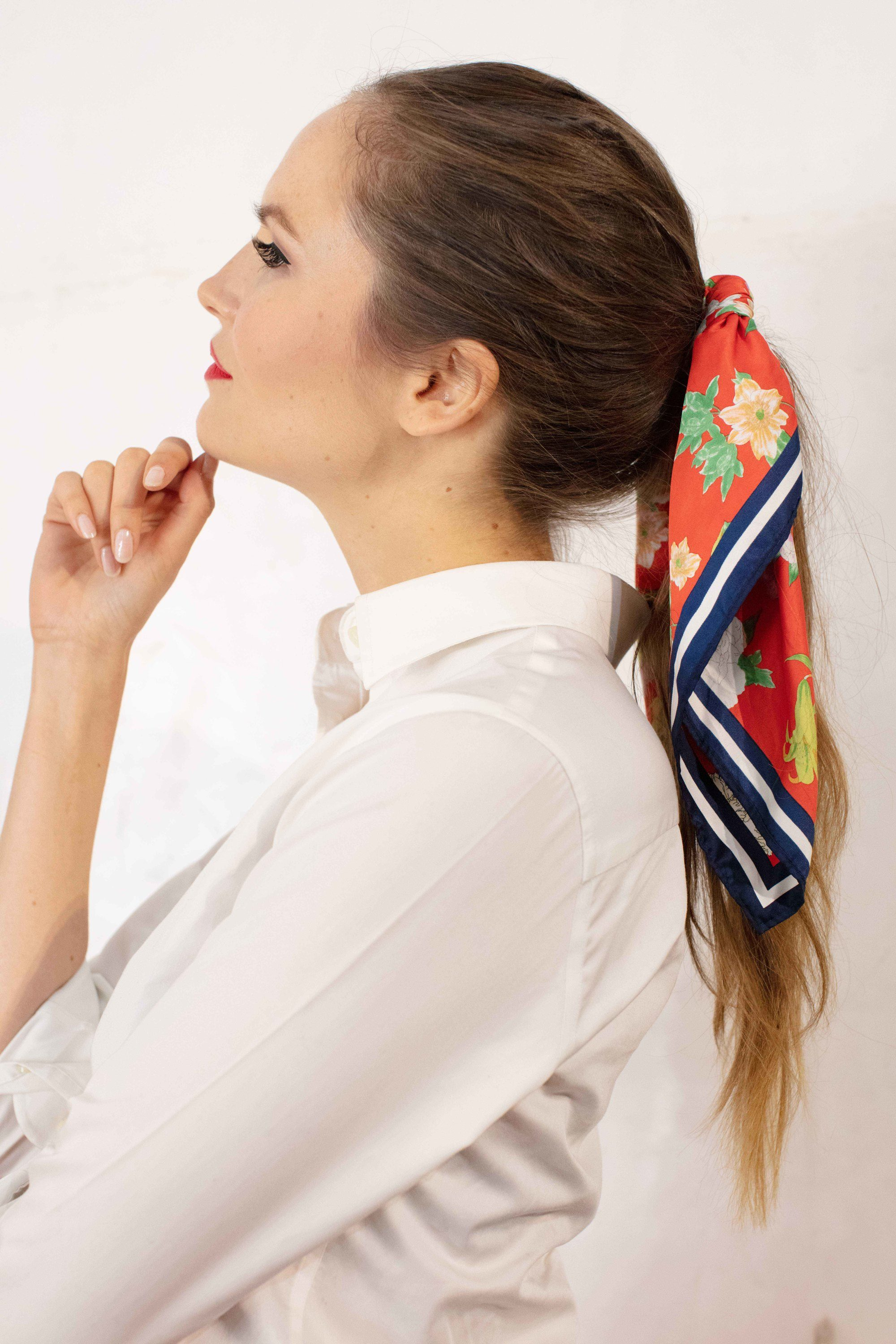 Retro hairstyles: Close up shot of a woman with medium brown long hair styled into a retro ponytail with a scarf backstage at Goodwood festival