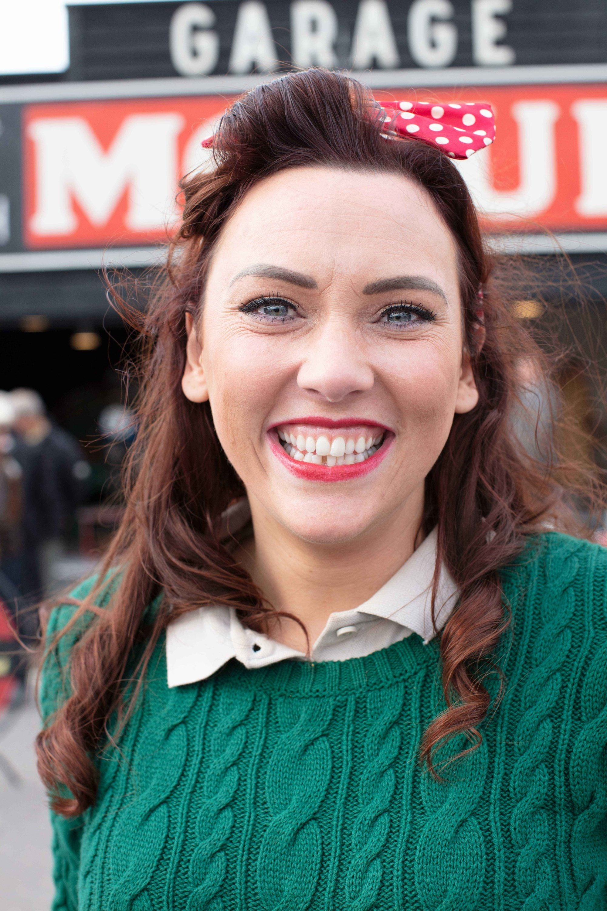 Pin up hairstyles: Smiling woman at Goodwood Revival with dark red curly hair in a half-up victory rolls style