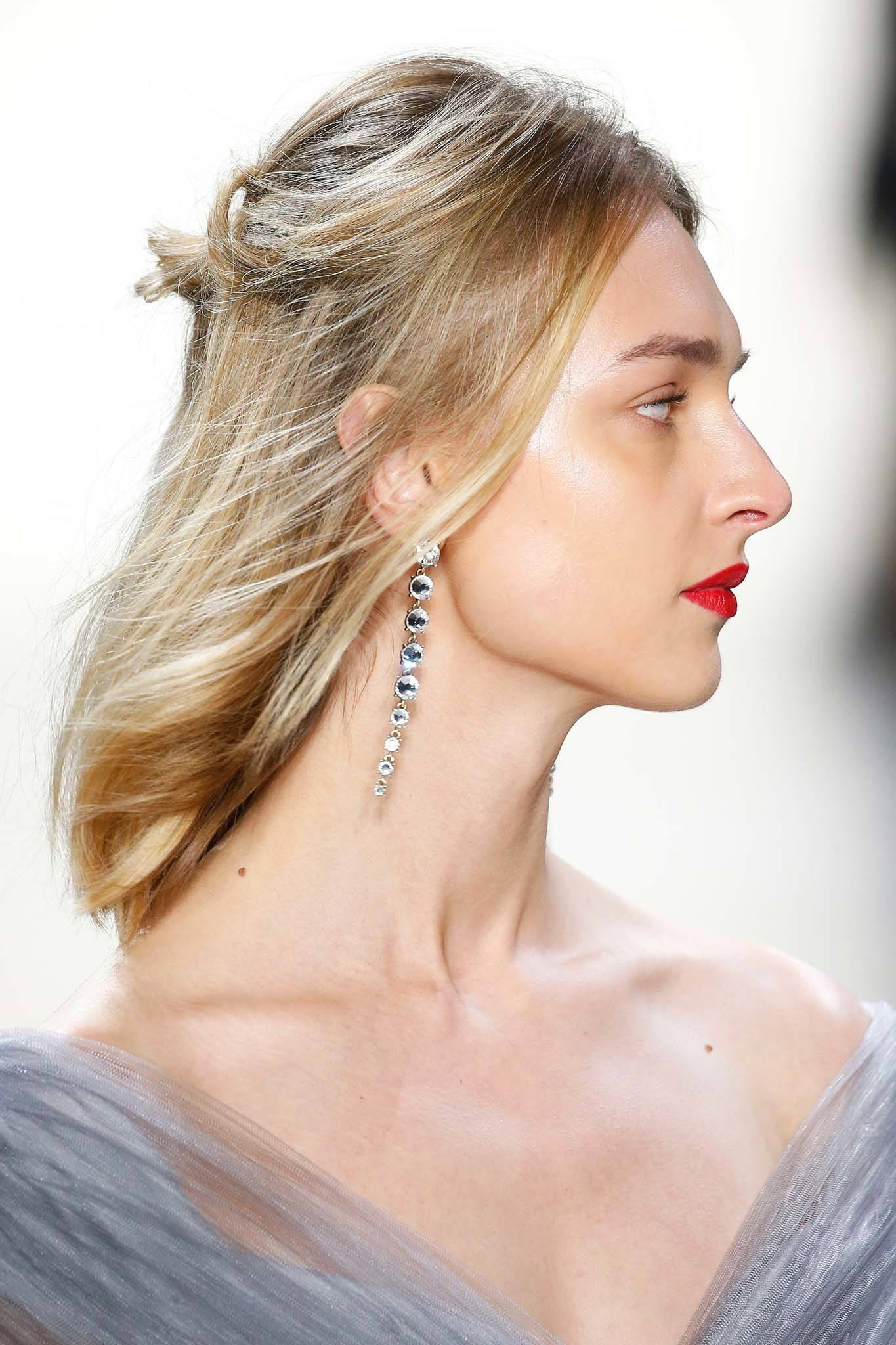 NYFW Catwalk Trends: Model on Tadashi Shoji FW18 runway with shoulder length blonde straight hair in half-up, half-down messy bun wearing red lipstick and diamond drop earrings.