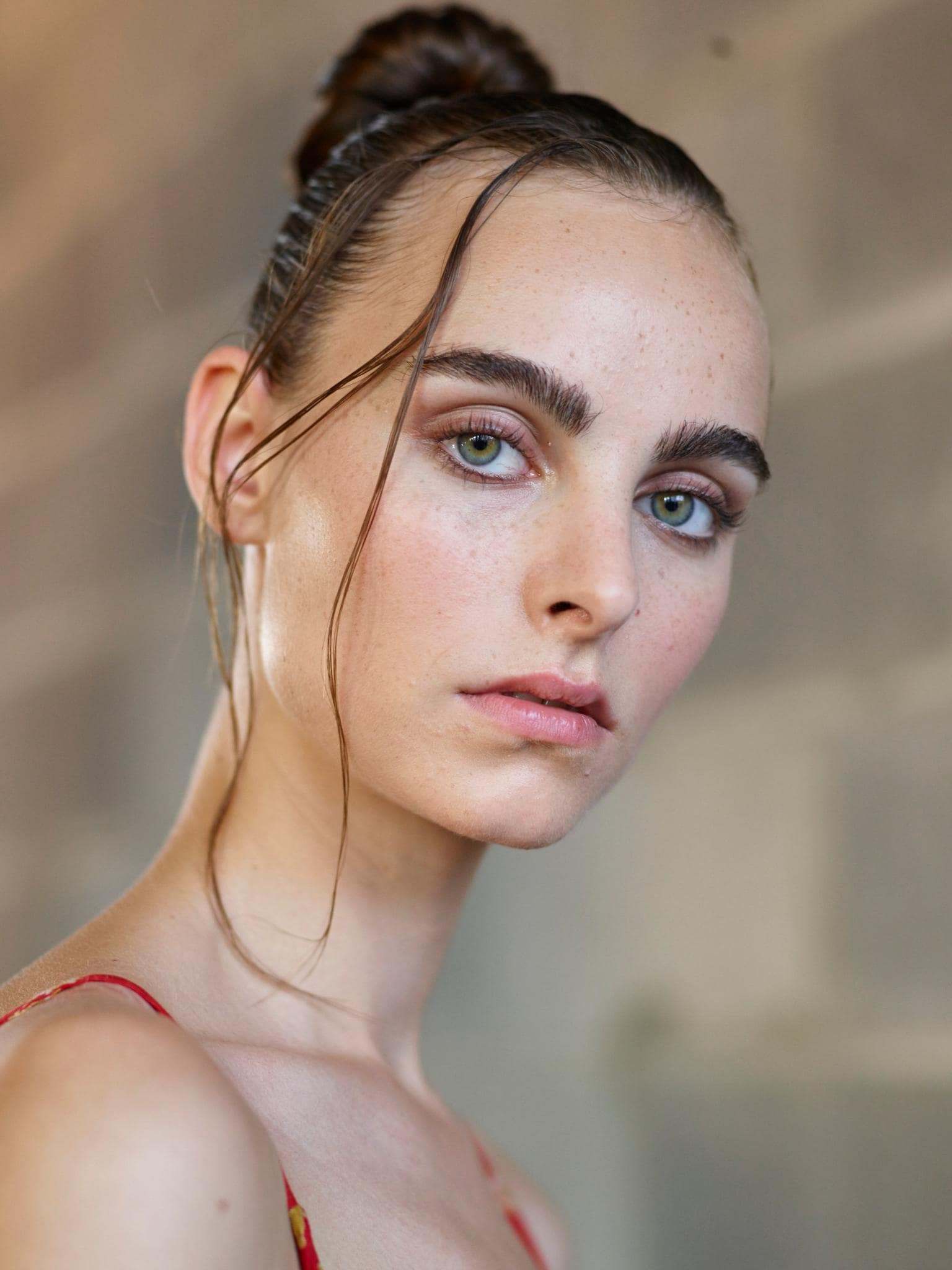 Knot bun hairstyle: Brunette model at Thakoon with a wet look top knot hairstyle