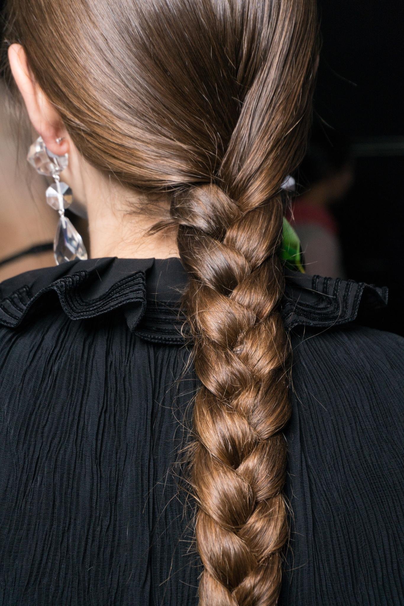 NYFW Catwalk Trends: Woman at Tory Nurch FW18 show with long brown hair in single three strand braid wearing a black top.