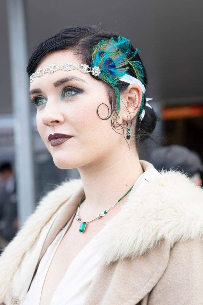 Photo of a woman with dark brown almost black hair in a low bun with a 1920s inspired peacock feather headband, wearing vintage clothing