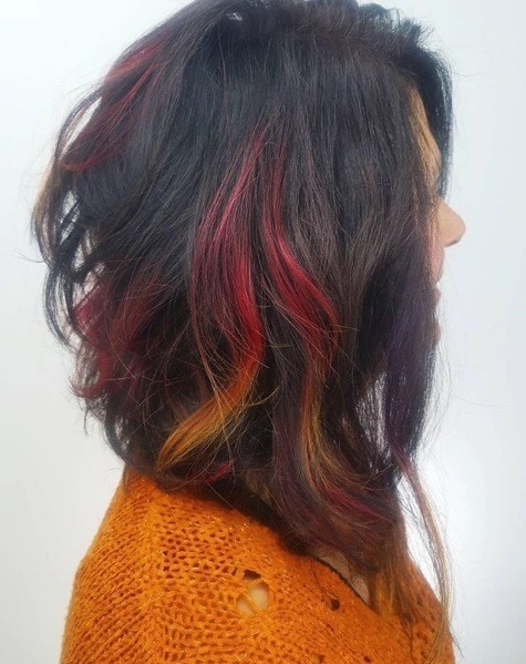 Fireworks hair colours: Side profile of a woman with a dark brunette A-line bob with a streak of red and orange