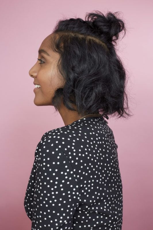 How to braid short hair: Side profile photo of All Things Hair Global Senior Producer Elise with a half-up braided bun and wavy bob