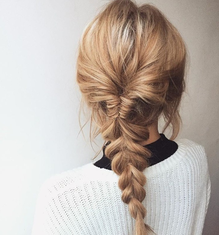 Bonfire hairstyles: Back shot of woman with bronde long hair styled into a braided ponytail, wearing white jumper with black turtleneck underneath it