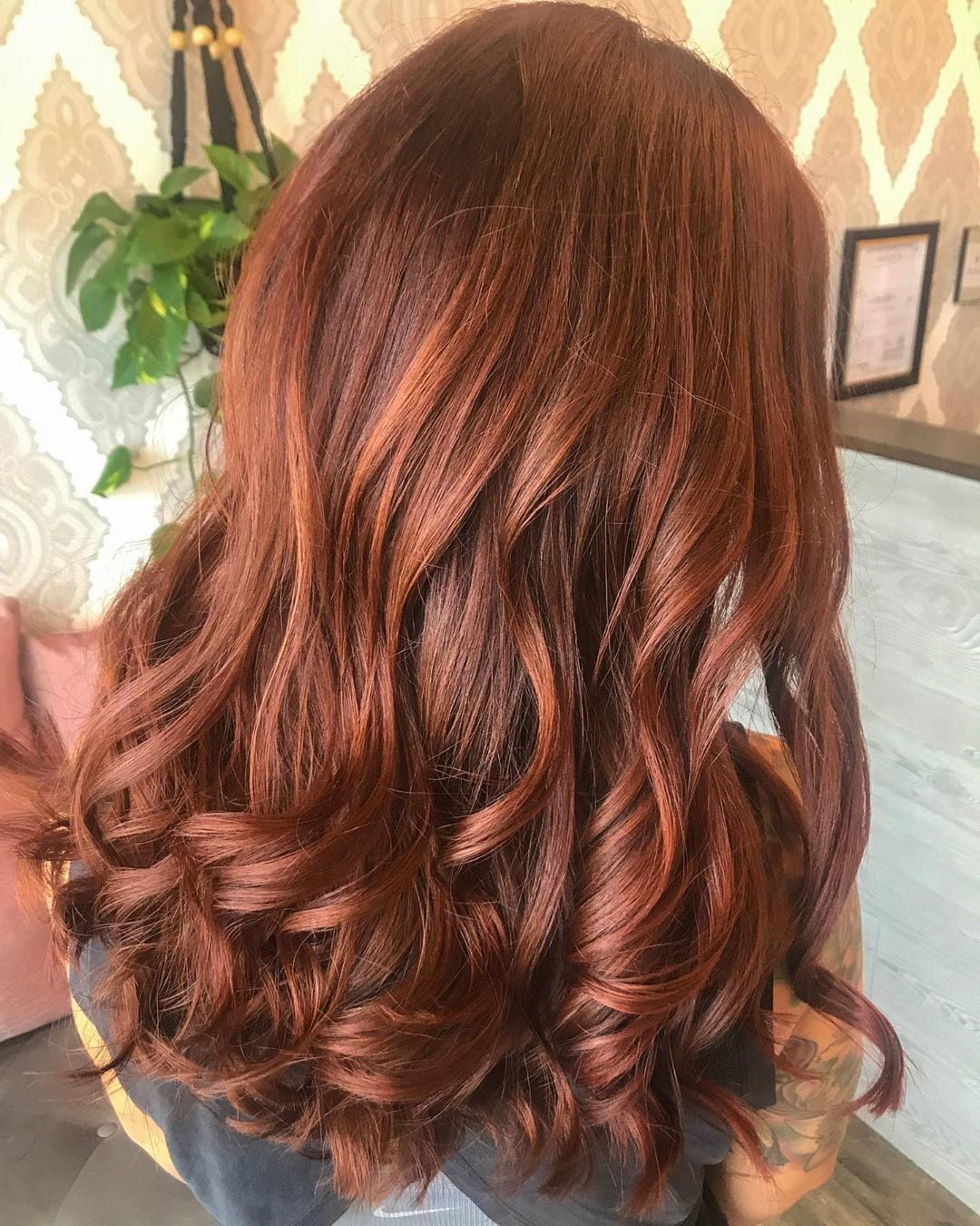 Woman with long, curly cinnamon hair with pumpkin spice tones in it