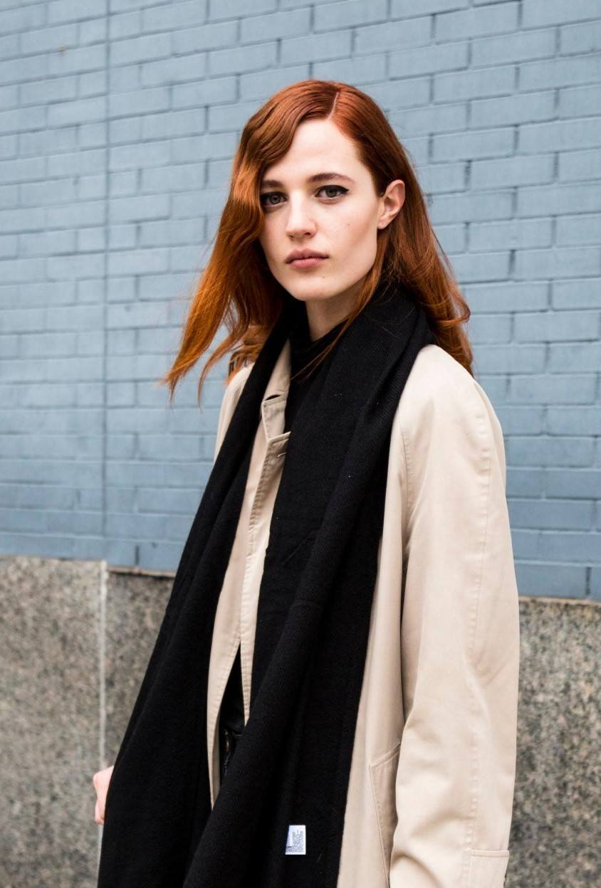 2019 hair colour trends: Street style shot of a woman with copper shoulder length hair with retro curls, wearing a black scarf and beige coat