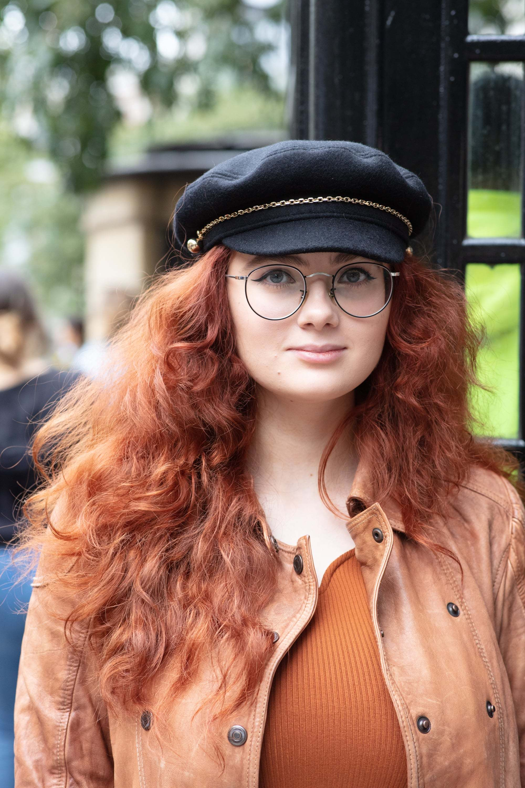 Hair treatment guide: Woman with long curly copper hair, wearing beige jacket with a baker boy hat