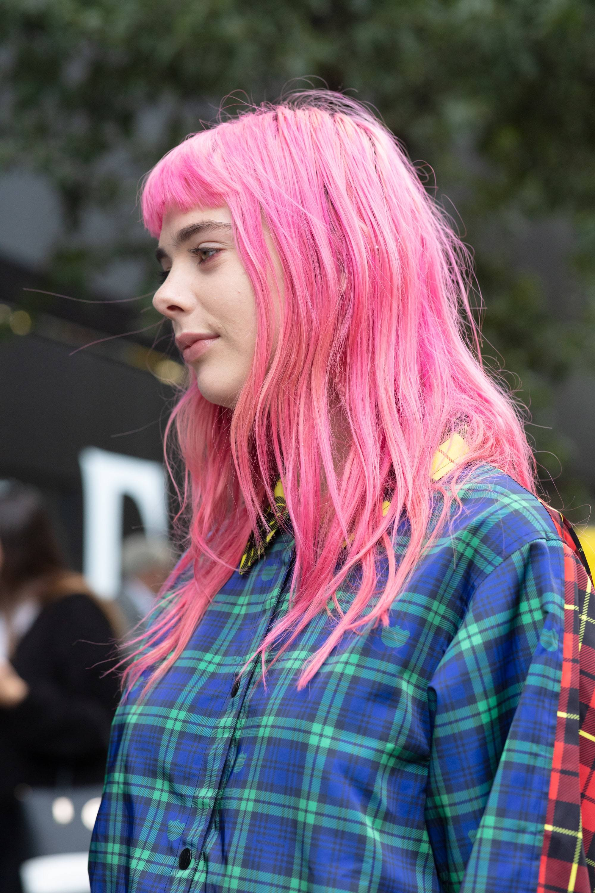 Hair treatment guide: Woman with medium neon pink hair with a micro fringe, wearing checked shirt