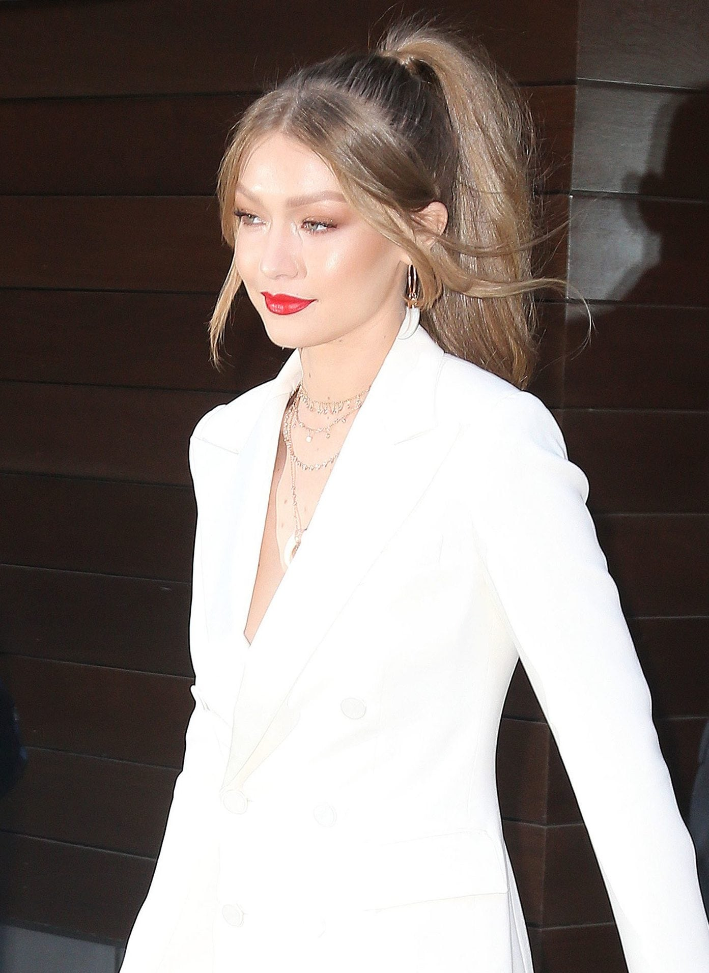 Winter hairstyles 2018: Out and about shot of Gigi Hadid with her dirty blonde hair in a ponytail with Bardot style wispy fringe, wearing a white two-piece suit
