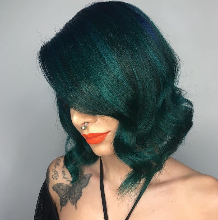Halloween hair colour: Woman with dark emerald green short hair styled into waves at the end, wearing orange lipstick with a Bardot top in a studio