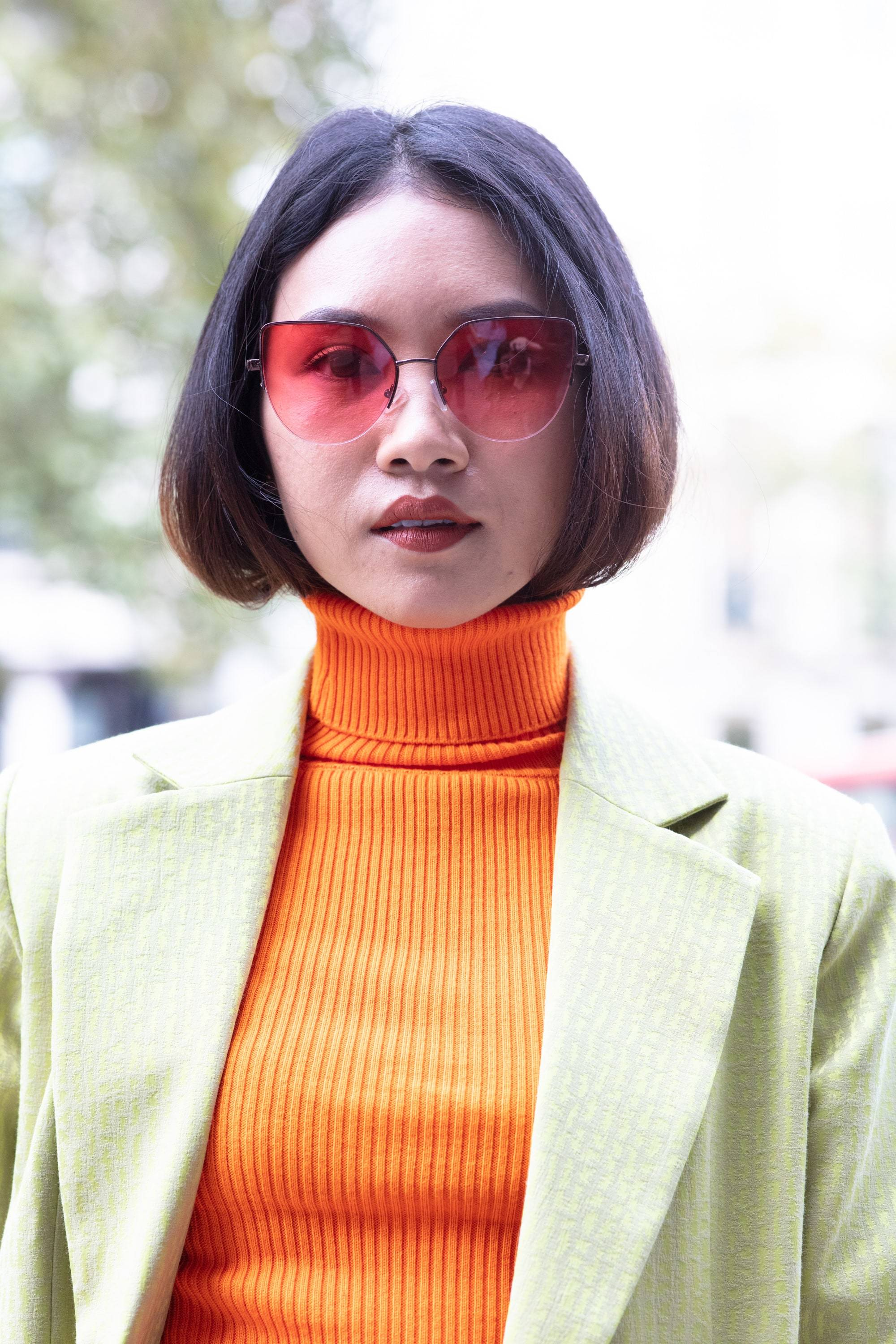 Bonfire hairstyles: Shot of a woman with straight hair tucked into her orange turtleneck, wearing lime green blazer and posing outside