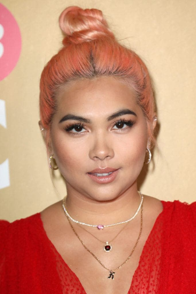 2019 hair colour trends: Hayley Kiyoko with orangey peach hair worn in a top knot, wearing a red dress and necklaces