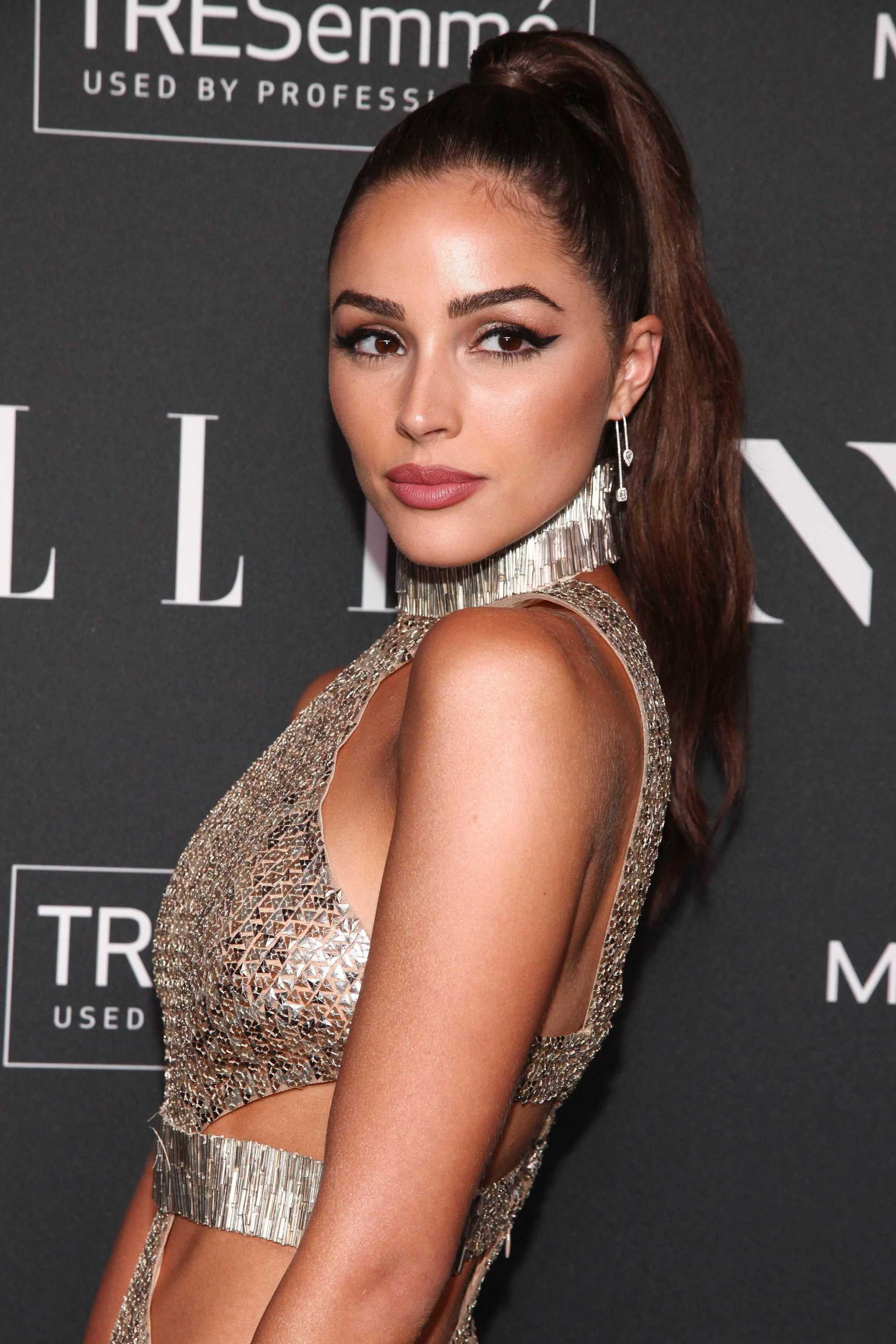 Winter hairstyles 2018: Olivia Culpo with her dark chocolate hair in a glamorous wrapped high ponytail, wearing a metallic mesh cut-out dress