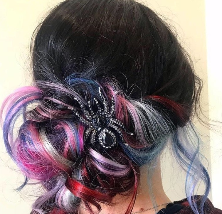 Halloween hair accessories: Woman dark purple ombre hair styled into a low messy bun with spider clip