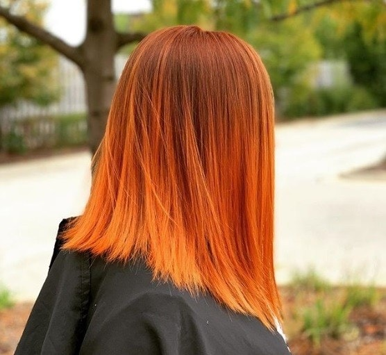 Halloween hair colour: Side shot of woman with pumpkin spice hair colour, wearing black jacket and posing in a woodland setting
