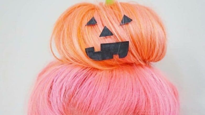 Halloween hair colour: Close up shot of woman with bubblegum pink hair to pastel orange ombre styled into a messy bun, with pumpkin decoration on it