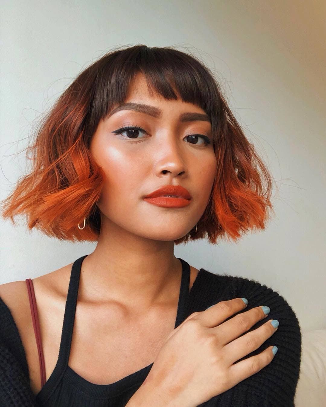 Woman with short bob with bangs with pumpkin spice ombre ends