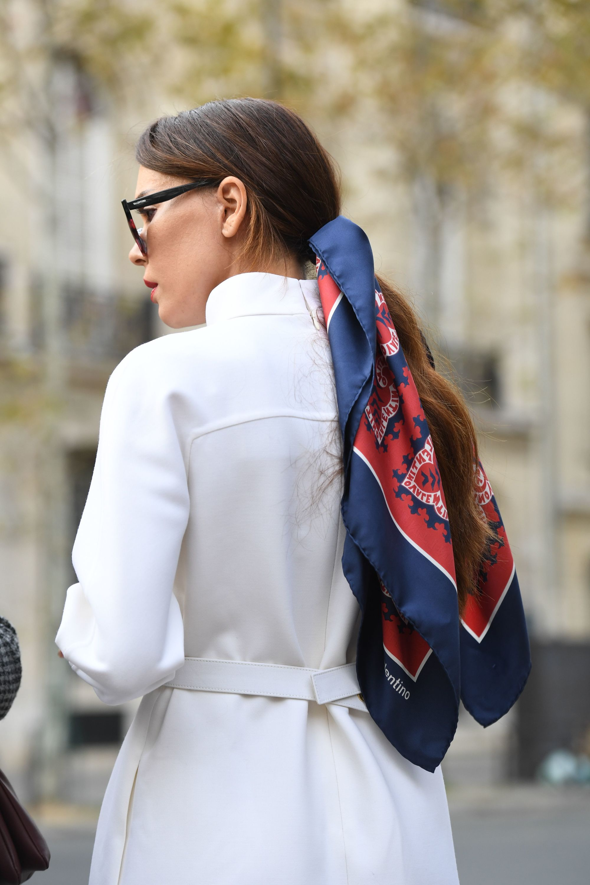 Winter hairstyles 2018: Back view of a brunette street styler with a long low ponytail tied with a blue and red patterned hair scarf