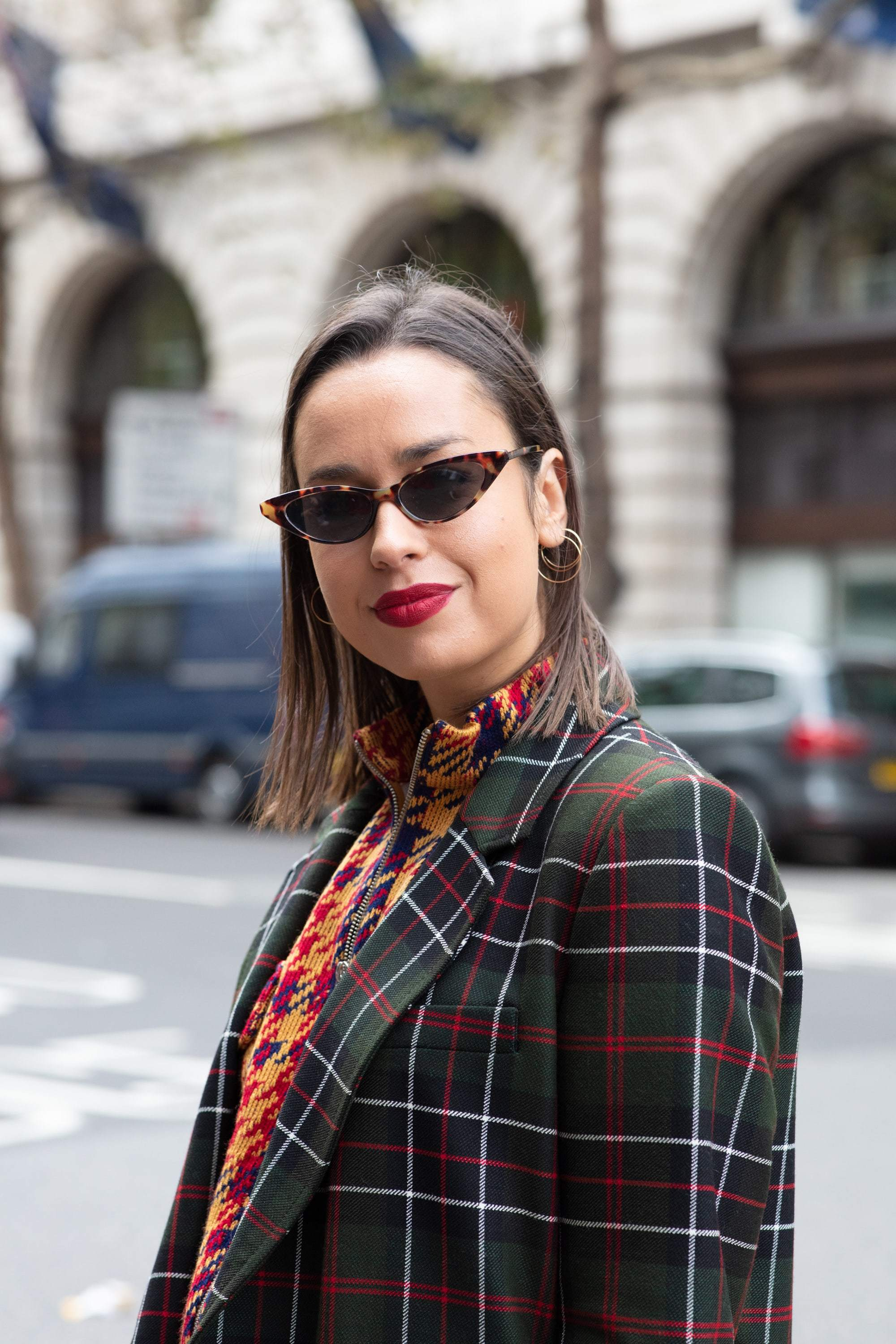 Hair treatment guide: Woman with blunt cut chestnut long bob, wearing checked jacket with tiny glasses
