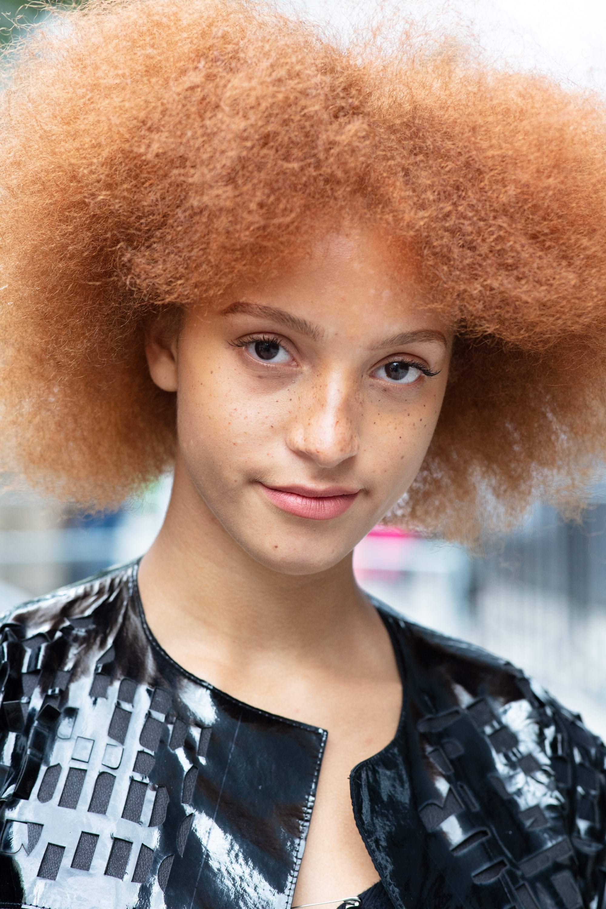 Hair treatment guide: Woman with big, fluffy ginger afro wearing black jacket outside on the street