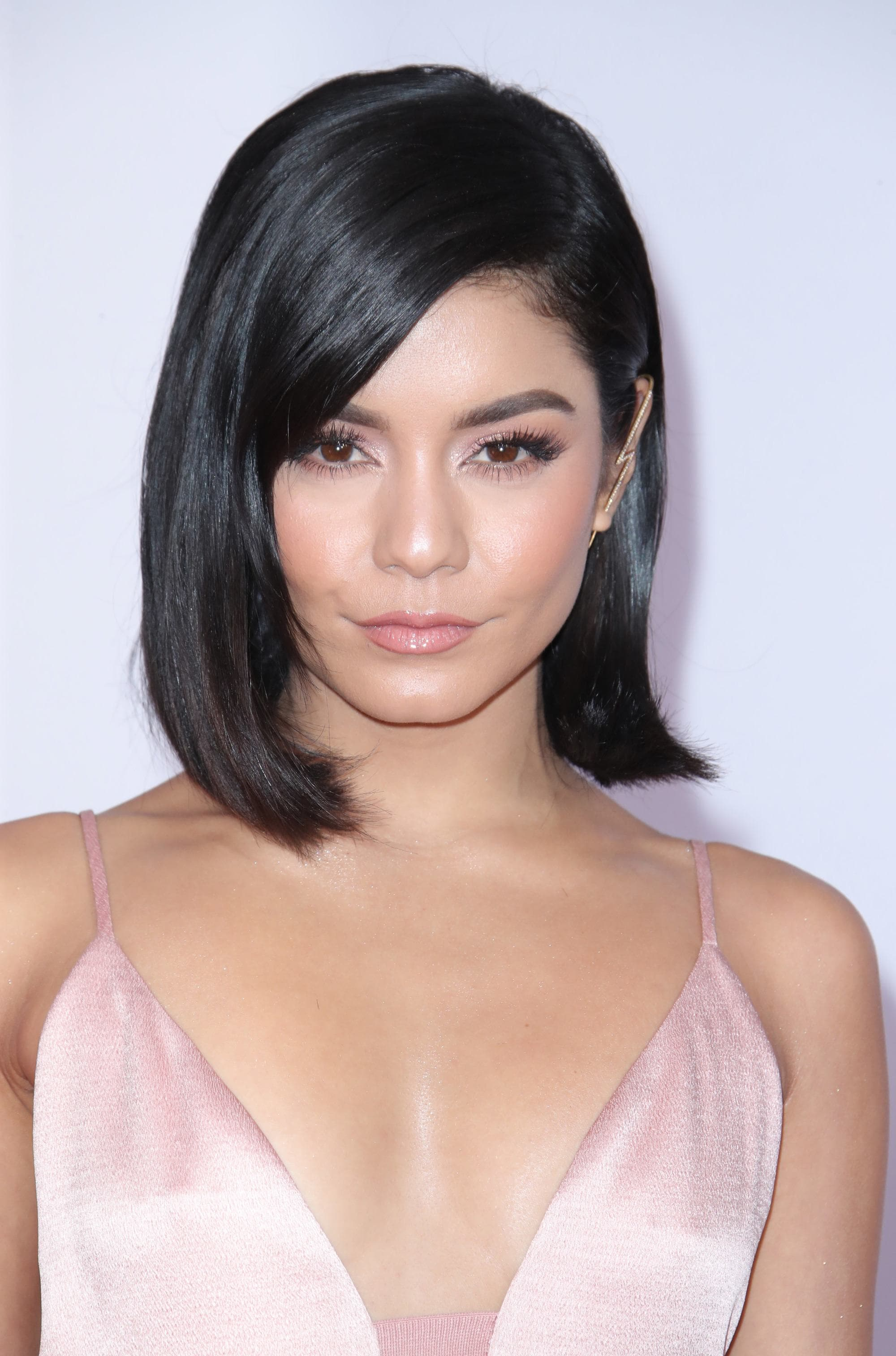 Winter hairstyles 2018: Vanessa Hudgens at the 2018 AMAs with a sleek shiny bob with a side parting, wearing a soft pink silky cami dress