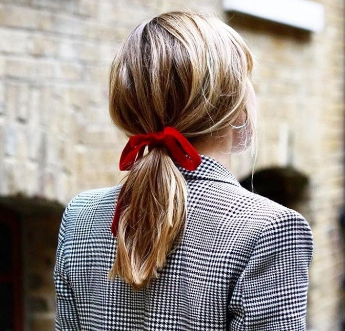 Bonfire hairstyles: Back shot of woman with bronde medium length hair styled into a low ponytail and tied up with a red bow, wearing a checked blazer and posing outside