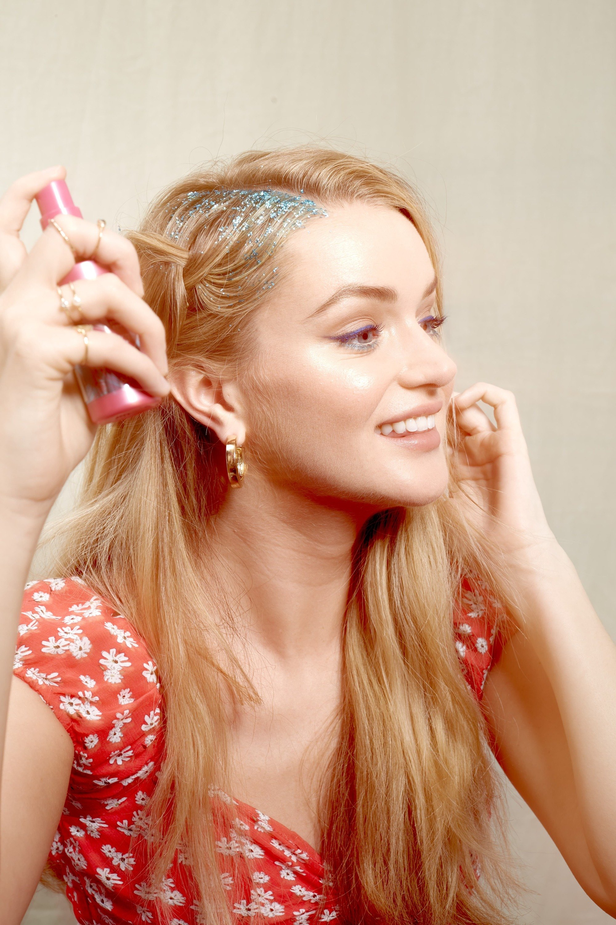 Blonde woman with braided glitter roots spraying fixing spray