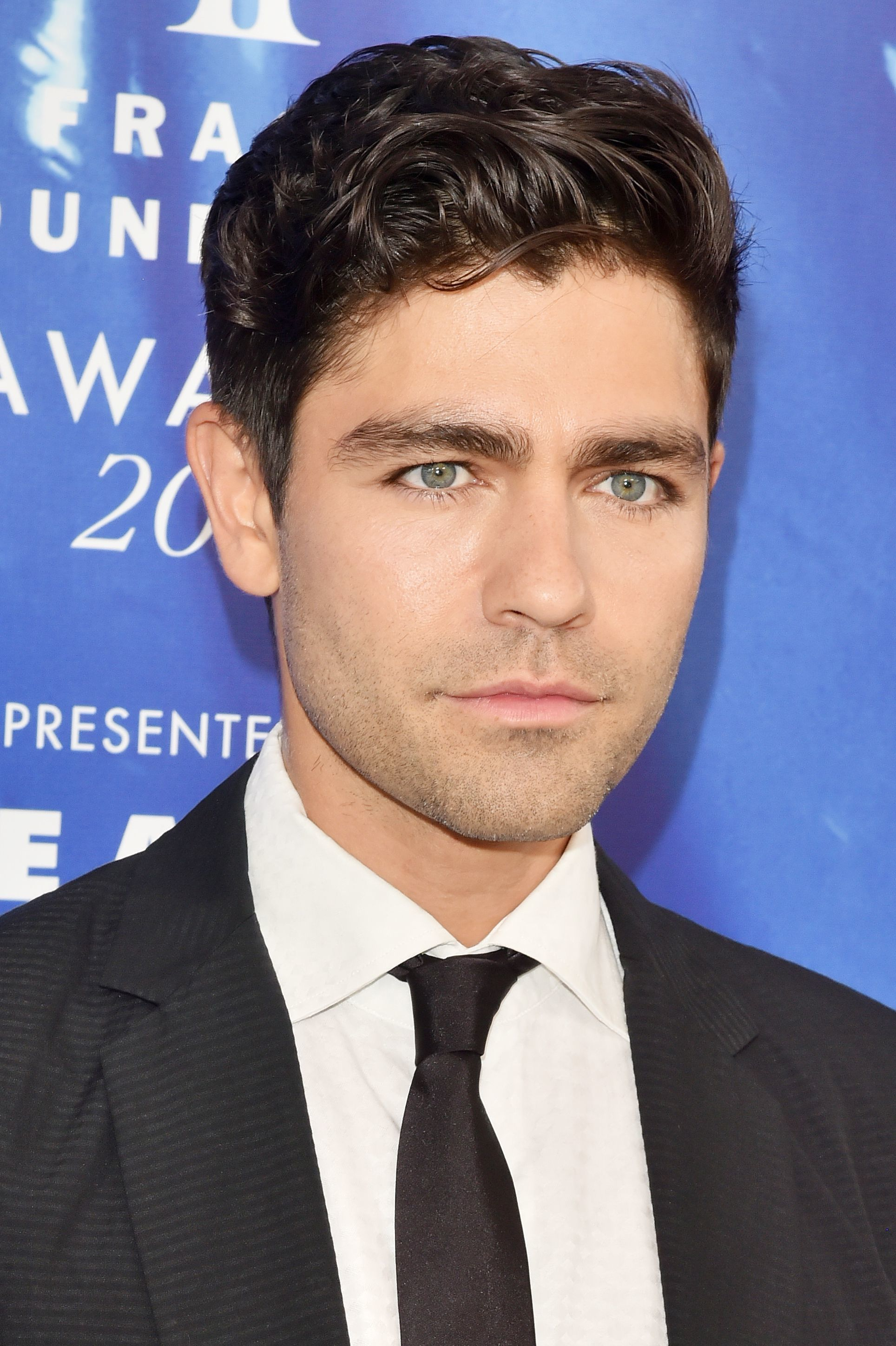 Hairstyles for men over 40: Headshot of Adrian Grenier with dark wavy hair, wearing a suit and tie