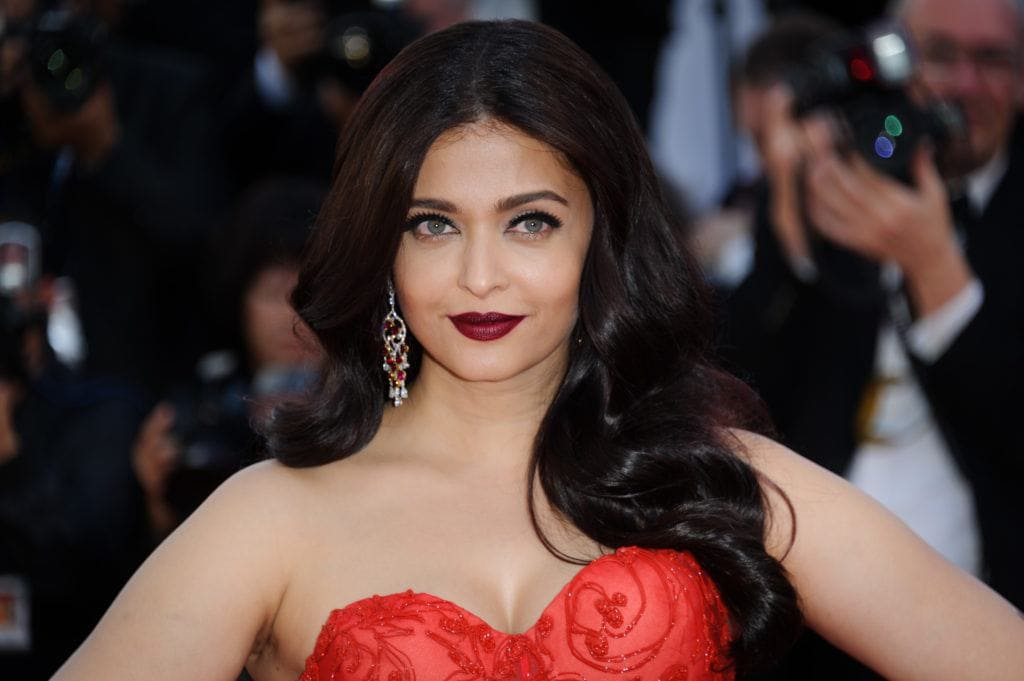 Bollywood hair: Aishwarya Rai with dark brown hair with burgundy tones, styled into Hollywood waves, wearing red dress on the red carpet
