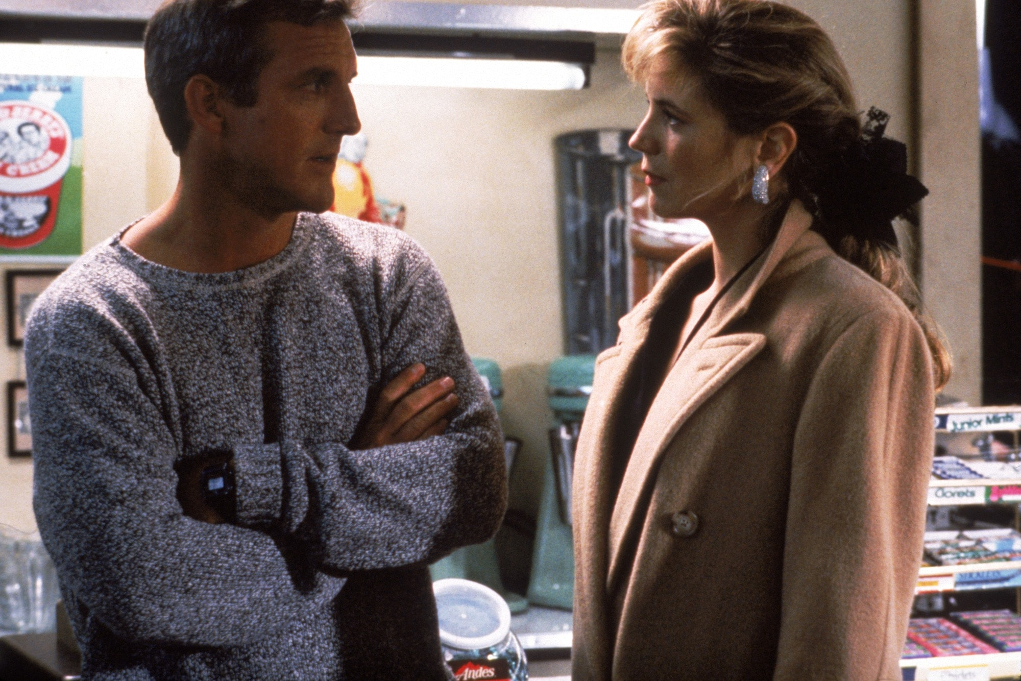 All I Want for Christmas: Jane Kozak as Catherine O'Fallon, with her bronde hair styled into low ponytail with a bow, wearing a statement earring and camel coat on set, while talking to Micheal O'Fallon